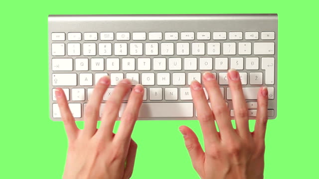 Female hands typing on keyboard against green screen