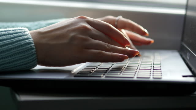 Female hands typing on keyboard of laptop in train. Woman chatting with friends during traveling on railway. Young girl using notebook. Arm print a message. Close up video
