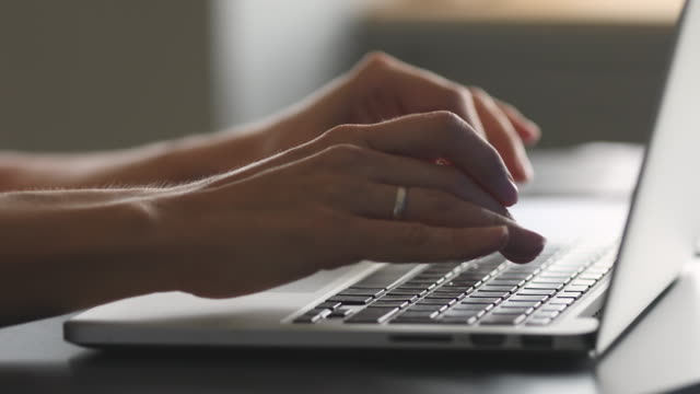 female hands typing on laptop at desk, close up view - didattica a distanza video stock e b–roll