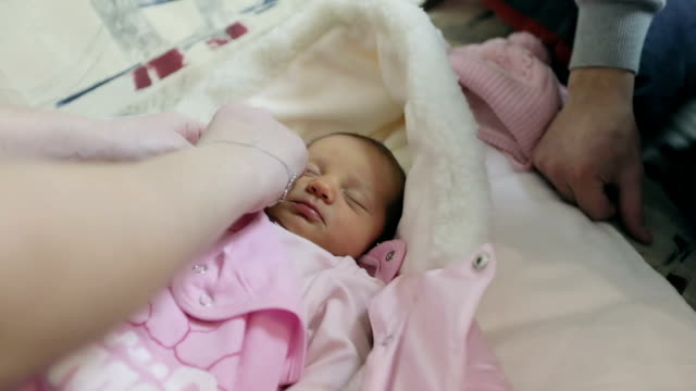 Female hands undress newborn baby girl. video