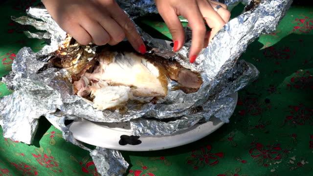 stockvideo's en b-roll-footage met vrouwelijke handen uitpakken verse vis gebakken in folie in outdoor open haard gloeiende. 4k - carp