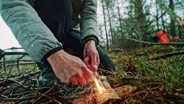 SLO MO Female hands using a fire striker to start a fire in the wilderness Slow motion close up locked down shot of the hands of a woman using a Ferrocerium rod to start a fire in nature. Shot in Slovenia. stick plant part stock videos & royalty-free footage