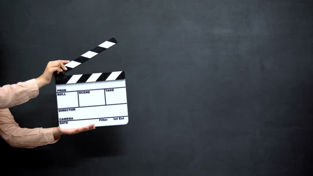 Female hands using clapperboard against black background, shooting movies Female hands using clapperboard against black background, shooting movies multimedia stock videos & royalty-free footage