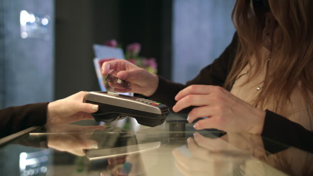 vídeos de stock e filmes b-roll de female hands using plastic card at hotel reception. woman paying by credit card - paying with card contactless