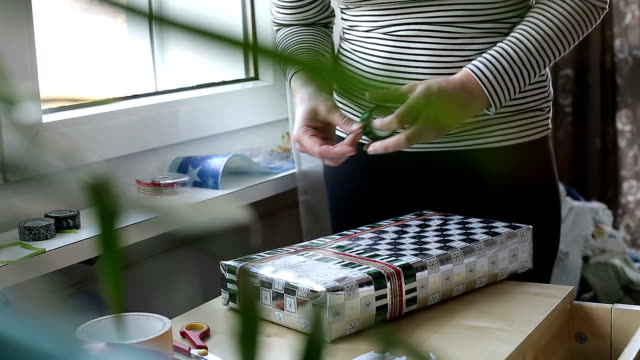 Female hands with a scotch tape are packing gift video