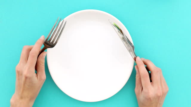 vidéos et rushes de mains féminines avec couverts et assiette vide - fourchette
