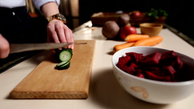 Female hands with knife cutting cucumber on board video