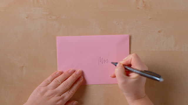 SLO MO LD Female hands writing on a pink envelope