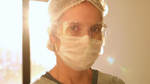 vidéos et rushes de verticale de travailleur de santé féminin avec le soleil sur le fond - medecin covid