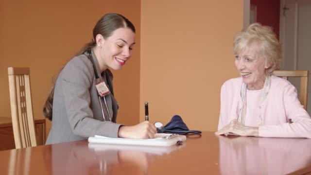 vídeos y material grabado en eventos de stock de mujer profesional de la salud pide preguntas de mujer senior - geriatría