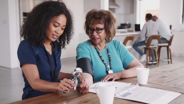 Female healthcare worker checking the blood pressure of a senior woman during a home visit Female healthcare worker checking the blood pressure of a senior woman during a home visit blood pressure gauge stock videos & royalty-free footage