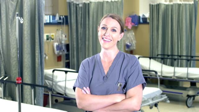 vidéos et rushes de travailleuse de santé restant dans le service d'hôpital - une seule femme d'âge mûr