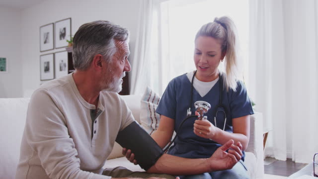 Female healthcare worker taking the blood pressure of a senior man during a home health visit Female healthcare worker taking the blood pressure of a senior man during a home health visit blood pressure gauge stock videos & royalty-free footage