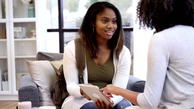 Female high school guidance counselor advises teenage girl Confident mature African American female high school guidance counselor shows an African American teenage girl something on a digital tablet. The teenager nods and smiles as she looks at the tablet and listens to the counselor. school counselor stock videos & royalty-free footage