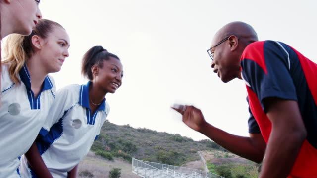 squadra sportiva femminile del liceo e allenatore che parla di squadra - allenatore video stock e b–roll