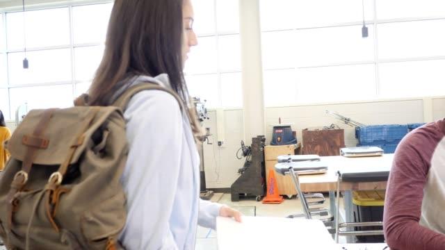 kadın lise öğrencisi sınıfta yürür - sırt çantası stok videoları ve detay görüntü çekimi