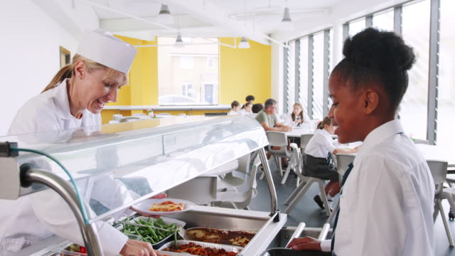 female high school student wearing uniform being served food in canteen - stołówka filmów i materiałów b-roll
