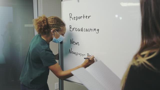 Female High School Student writing on whiteboard in Classroom Setting Wearing Mask 4K Video