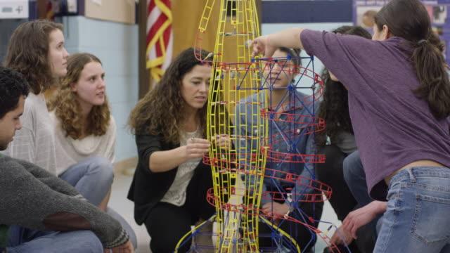 weibliche high school lehrer präsentiert auf einer achterbahn modell - highschool lehrer stock-videos und b-roll-filmmaterial