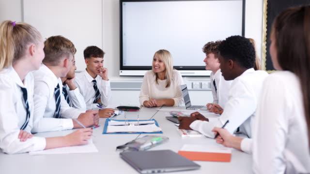 kobieta nauczycielka w szkole średniej siedząca przy stole z nastoletnimi uczniami ubranymi w jednolitą lekcję nauczania - uniform filmów i materiałów b-roll