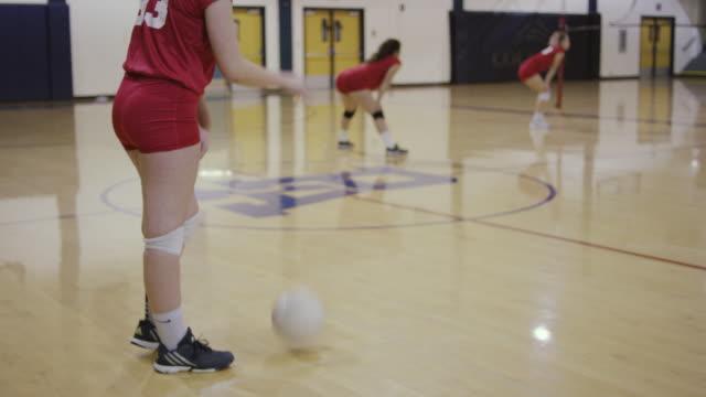 Joueuse de volley-ball féminin du lycée s'apprête à servir le volley-ball pendant un match - Vidéo