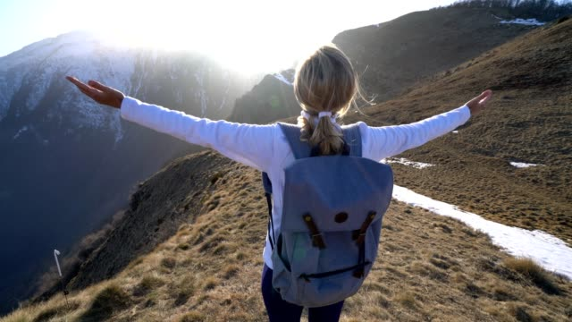 Female hiker arms outstretched on top of mountain video