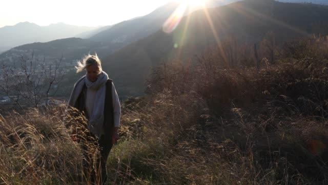 vidéos et rushes de randonneuse monte pente herbeuse au lever du soleil - évasion du réel