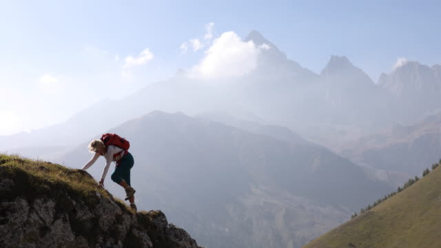 female hiker ascends mountain ridge above valley - pantaloni capri video stock e b–roll