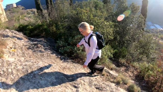 stockvideo's en b-roll-footage met vrouwelijke wandelaar stijgt steile parcours bij zonsopgang - handen op de heupen