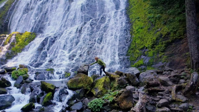 Female Hiker Climbing Over Rocks Beneath Massive Waterfall video