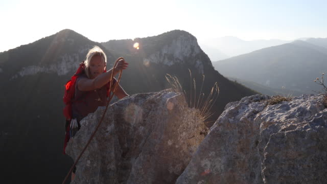 Female hiker climbs along mountain summit at sunrise She tentatively follows knife edge ridge, attached to rope, Liguria pedal pushers stock videos & royalty-free footage
