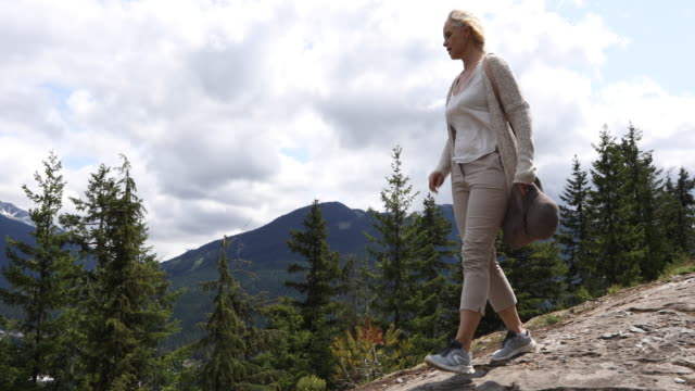 female hiker descends mountain slope above valley, ski area - pantaloni capri video stock e b–roll