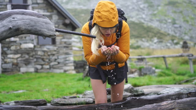 Female hiker drinks from mountain fountain on foggy day Exploring the mountains of Ticino, Switzerland fountains stock videos & royalty-free footage