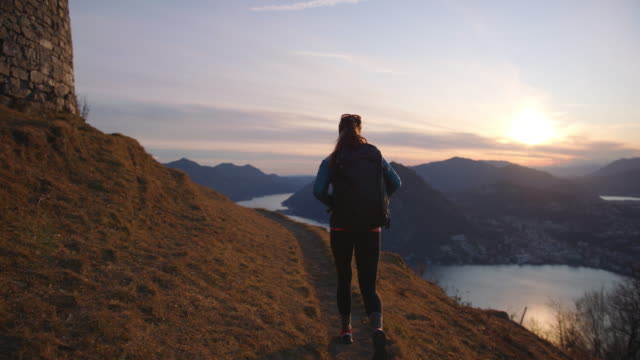 Female hiker follows trail to mountain top with view of city, lake and sunset below