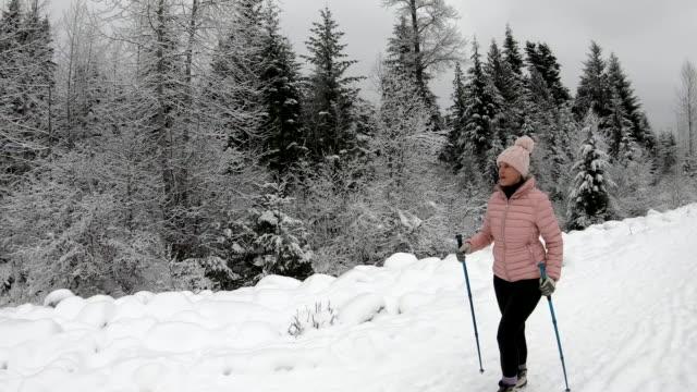 vídeos de stock e filmes b-roll de female hiker follows winter path through snowy forest - 55 59 anos