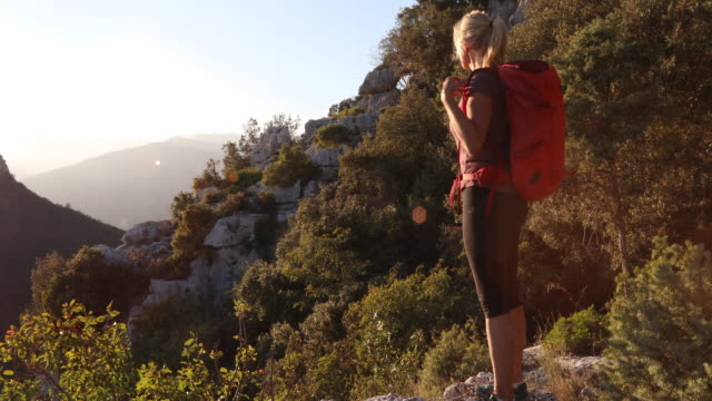 Female hiker hikes along treed edge at sunrise She looks off to distant scene,  Liguria pedal pushers stock videos & royalty-free footage