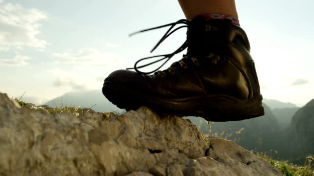 CLOSE UP Female hiker in mountaineering boots walking up the rocky mountain