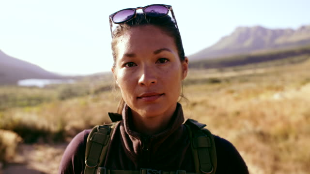 Female hiker in nature reserve Video of asian woman with backpack and sunglasses standing in countryside and smiling. Female hiker in nature reserve looking at camera and smiling. candid stock videos & royalty-free footage