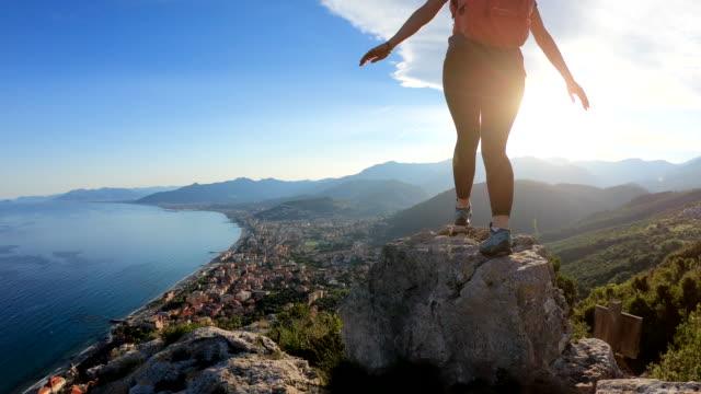 female hiker jumps between rocks at sunrise - położenie filmów i materiałów b-roll