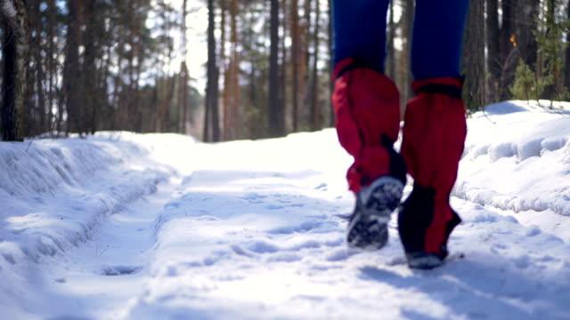Female hiker legs walking on a snow road. video