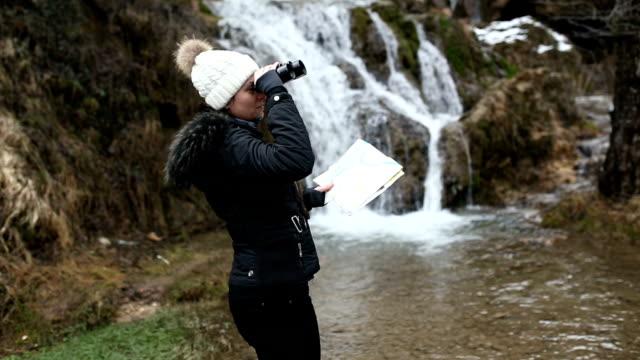 kvinnliga hiker tittar på vattenfall. - endast unga kvinnor bildbanksvideor och videomaterial från bakom kulisserna