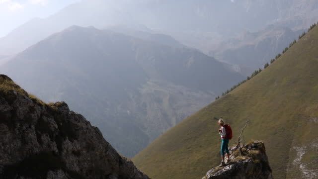 female hiker looks out from mountain ridge, above valley - pantaloni capri video stock e b–roll