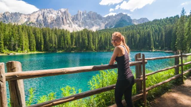 vídeos de stock, filmes e b-roll de feminino caminhante sobre caminhadas no lago de montanha, admirando a vista das montanhas, sorrindo para a câmera - tyrol state austria