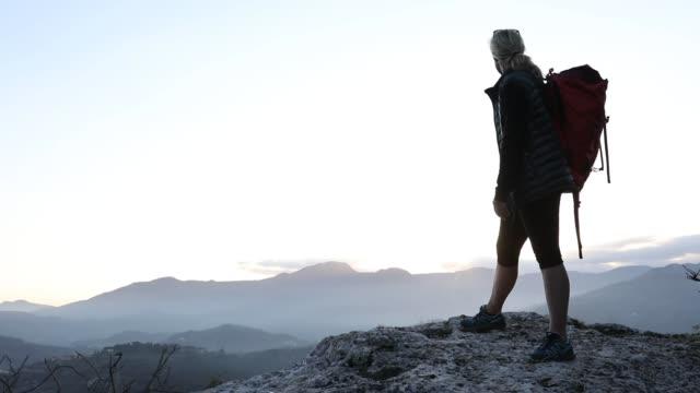 vidéos et rushes de randonneuse s'arrête au-dessus de la vallée au lever du soleil - évasion du réel