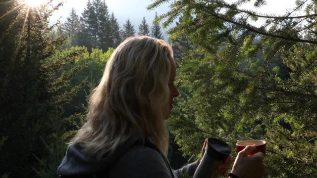 kvinnliga hiker häller varm dryck i skog, vid soluppgången - endast en medelålders man bildbanksvideor och videomaterial från bakom kulisserna