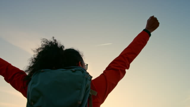 vídeos de stock, filmes e b-roll de slo mo caminhante fêmea chegando ao topo da montanha e levantando as mãos na vitória ao pôr do sol - aventura