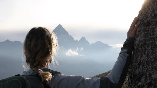 vídeos de stock, filmes e b-roll de o caminhante fêmea relaxa acima do prado alpino no nascer do sol - distante