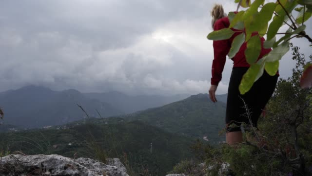 female hiker relaxes above valley and mountains on stormy day - pantaloni capri video stock e b–roll