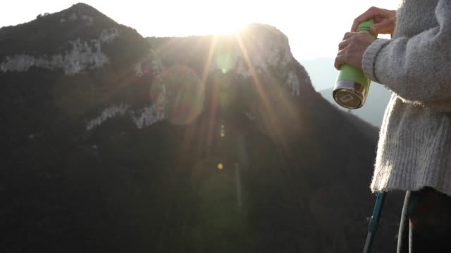 Female hiker relaxes above valley at sunrise video