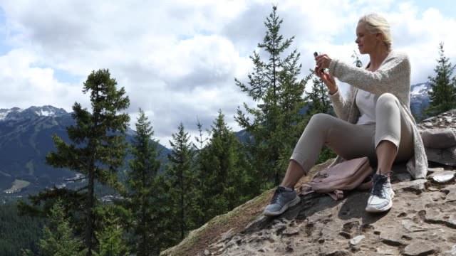 female hiker relaxes on mountain slope above valley, ski area - pantaloni capri video stock e b–roll